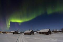 Byhus i ljusen av månen och norrsken Arkivfoto