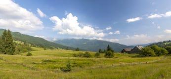 Byhus på kullar med gröna ängar i sommardag Royaltyfri Foto