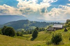 Byhus på kullar med gröna ängar i sommardag Arkivfoto