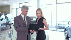 Bying a car, vehicle dealer explaining car specifications to buyer woman. stock video