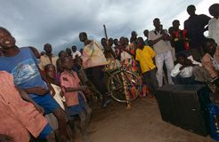 Byinvånare som lyssnar till pedal-drivit, radiosände, Uganda Arkivbilder