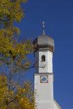 Bykyrka i gmund, guld- bokträdsidor och blå himmel som är bavar Arkivfoton