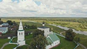 Bylandskap - tre olika kyrkor i byn och floden på en bakgrund - Suzdal, Ryssland stock video