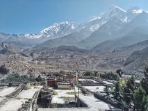 Byn i klyftan av den Kali Gandaki floden med höga klippor och dalen och några snöar korkade berg i bakgrunden arkivfoton