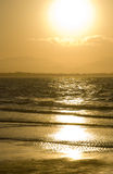 Byron Bay Golden Sunset. Golden sunset on the beach with dazzling reflections in the ocean surf at Byron Bay  on the north coast of New South Wales Australia Royalty Free Stock Image