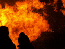 Bystanders watch the raging fire,silhouetted and blurry. Stock Photography