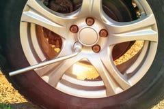 Byta ut hjulen på huvudvägen som skruva av muttrarna med en skiftnyckel royaltyfria bilder
