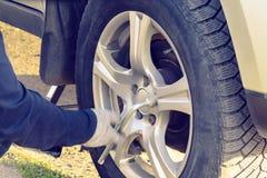 Byta ut hjulen p? huvudv?gen, silas bilen, m?nnens h?nder skruva av muttrarna med ett gummihjulj?rn arkivbild