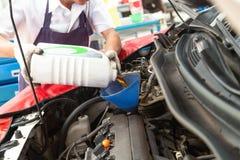 Bytande ut och hällande olja för bilmekaniker in i motorn på maintenanc royaltyfri foto