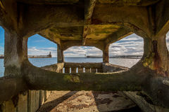Byth harbour viewed through pier foundations Stock Photos