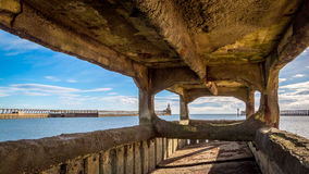 Byth harbour viewed through pier foundations Stock Images