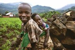 BYUMBA, RWANDA - 9 DE SEPTIEMBRE DE 2015: Niños no identificados El niño africano que lleva a su hermano con ella detrás Fotos de archivo libres de regalías