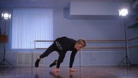 Byxa och sweater för stilig höft-flygtur dansare som iklädd svart utför handstans som en beståndsdel av urbanstyle och arkivfilmer