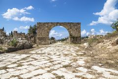 Byzantine road with triumph arch with blue sky in ruins of Tyre, Lebanon. Byzantine road with triumph arch with blue sky and clouds in ruins of Tyre, Lebanon Stock Photos