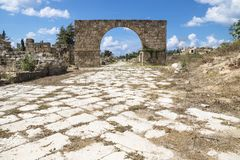 Byzantine road with triumph arch in ruins of Tyre, Lebanon. Byzantine road with triumph arch with blue sky in ruins of Tyre, Lebanon Royalty Free Stock Image