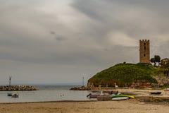 Byzantinischer Turm auf einem Hügel durch das Meer und gegen einen bewölkten Himmel Stockfoto