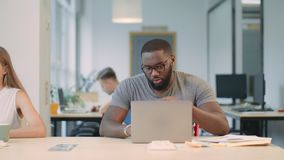 Cálculo de trabajo concentrado del ordenador portátil del hombre Letra inesperada de recepción masculina negra almacen de video