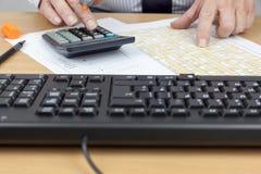 Cálculo ocupado de la cuenta financiera en su escritorio Imágenes de archivo libres de regalías