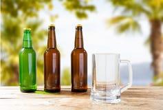 Cálice e garrafas vazios da cerveja na tabela de madeira no fundo das férias, na cidra do ofício e na cerveja borrados imagem de stock royalty free