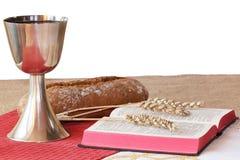 Cáliz de plata, biblia, pan en el fondo blanco fotografía de archivo