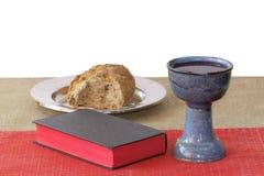 Cáliz de plata, biblia, pan en el fondo blanco fotos de archivo