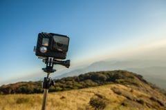 Cámara de la acción con el polo del selfie en el pico de la montaña Imagen de archivo libre de regalías