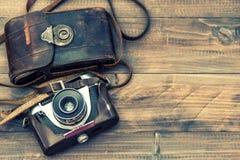 Cámara de la foto de la película del vintage con el bolso de cuero en fondo de madera Fotografía de archivo libre de regalías