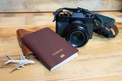 Cámara de la foto del artículo del viaje, pasaportes, en un piso de madera imagenes de archivo