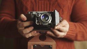 Cámara de la foto del vintage en las manos de metrajes