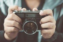 Cámara de la foto del vintage en las manos del hombre, foco suave Fotografía de archivo