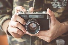 Cámara de la foto del vintage en las manos del hombre, foco suave Fotos de archivo