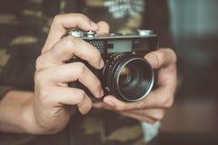 Cámara de la foto del vintage en las manos del hombre, foco suave Foto de archivo libre de regalías