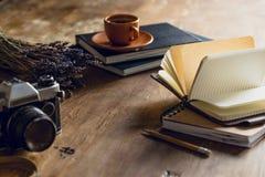 Cámara de la foto del vintage, y diarios y taza de café Fotos de archivo