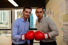 Cámara de la mirada de dos hombres de negocios con los guantes de boxeo Foto de archivo libre de regalías