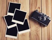 Cámara de la película del vintage y dos marcos en blanco de la foto en la tabla de madera Imagen de archivo