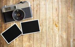 Cámara de la película del vintage y dos marcos en blanco de la foto en la tabla de madera Imágenes de archivo libres de regalías