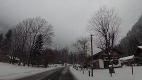 Cámara de la rociada en el coche, nieve en el centro turístico de montañas almacen de video