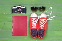 Cámara de los zapatos, de las gafas de sol, del cuaderno y de la película en la tabla de madera Imagen de archivo