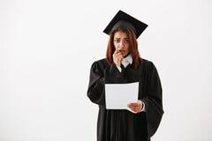 Cámara de mirada graduada descontentada triste de la hembra africana en que lleva a cabo la prueba sobre el fondo blanco Imagen de archivo