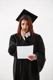 Cámara de mirada graduada descontentada triste de la hembra africana en que lleva a cabo la prueba sobre el fondo blanco Imagen de archivo libre de regalías