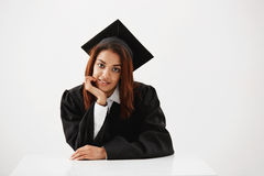 Cámara de mirada sonriente graduada de la hembra africana atractiva en que se sienta sobre el fondo blanco Fotografía de archivo libre de regalías