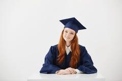 Cámara de mirada sonriente graduada de la hembra del pelirrojo en que se sienta sobre el fondo blanco Imágenes de archivo libres de regalías
