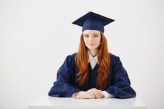 Cámara de mirada sonriente graduada de la hembra hermosa del pelirrojo en que se sienta sobre el fondo blanco Imagenes de archivo