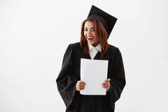Cámara de mirada sonriente graduada de la muchacha africana alegre feliz en que lleva a cabo la prueba sobre el fondo blanco Imagen de archivo libre de regalías