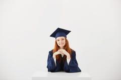 Cámara de mirada sonriente graduada del jengibre hermoso en que se sienta sobre el fondo blanco Fotografía de archivo
