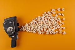 Cámara de película retra con las palomitas que vuelan de ellas en un fondo amarillo foto de archivo