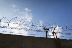 Cámara de seguridad detrás de la cerca del alambre de púas alrededor de las paredes de la prisión imágenes de archivo libres de regalías