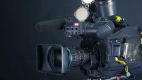 Cámara de vídeo digital profesional, cacoder aislado en fondo negro en srudio de la TV almacen de video