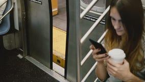 Cámara del alto ángulo en mujer europea joven atractiva en metro usando el smartphone, puertas de coche que se cierran en la plat metrajes