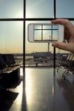 Cámara del teléfono celular que toma la imagen del aeropuerto moderno del salón de la salida Fotos de archivo